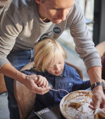 Kind eet een pannenkoek in het koerskaffee